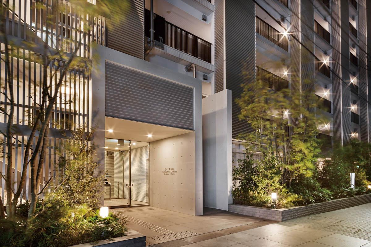 レジデンス棟エントランス完成予想図<br /> 緑に寄り添う佇まい[レジデンス棟]<br /> アプローチが並木道風の公開空地となるレジデンス棟は、緑を配して瀟洒な上質感を表現。背後に広がる住宅街と調和させています。