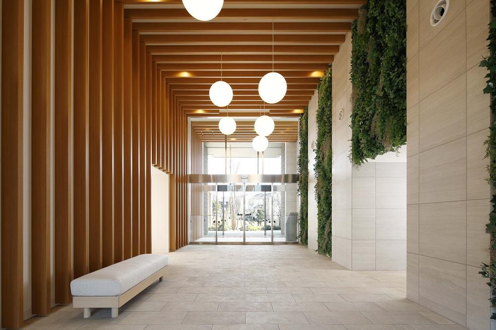 エントランスホール(2019年3月撮影)<br /> 二層吹き抜けで開放的なエントランスホール。アースカラーのタイル貼り壁面と、趣のある木調ルーバーとのコントラストが人を迎える場所のあたたかみを演出します。